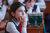 Fotografie Schoolchildren on the lesson in primary school. Girl looking at the teacher. Education in Russia. Selective focus