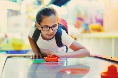 Cute teen girl plays air hockey arcade in game machine at an amusement park. stock vector