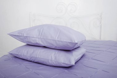 Bedclothes on the bed made with pillows.