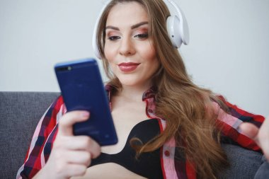 Beautiful pregnant woman with long hair in a plaid shirt is sitting on a gray sofa with a bare tummy, holding a smartphone in her hand and listening to music with headphones. Concept of happy motherhood, healthy lifestyle.