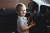 Lustiger kleiner Junge sitzt in der Kabine eines neuen Autos und ist glücklich. kaufen Sie einfach ein Auto im Händlercenter. das Konzept des Fahrzeugkaufs.