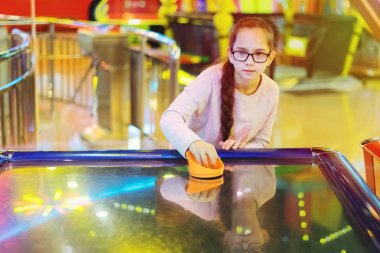 Young pretty girl in glasses with pigtails playing aero hockey on a slot machine. stock vector