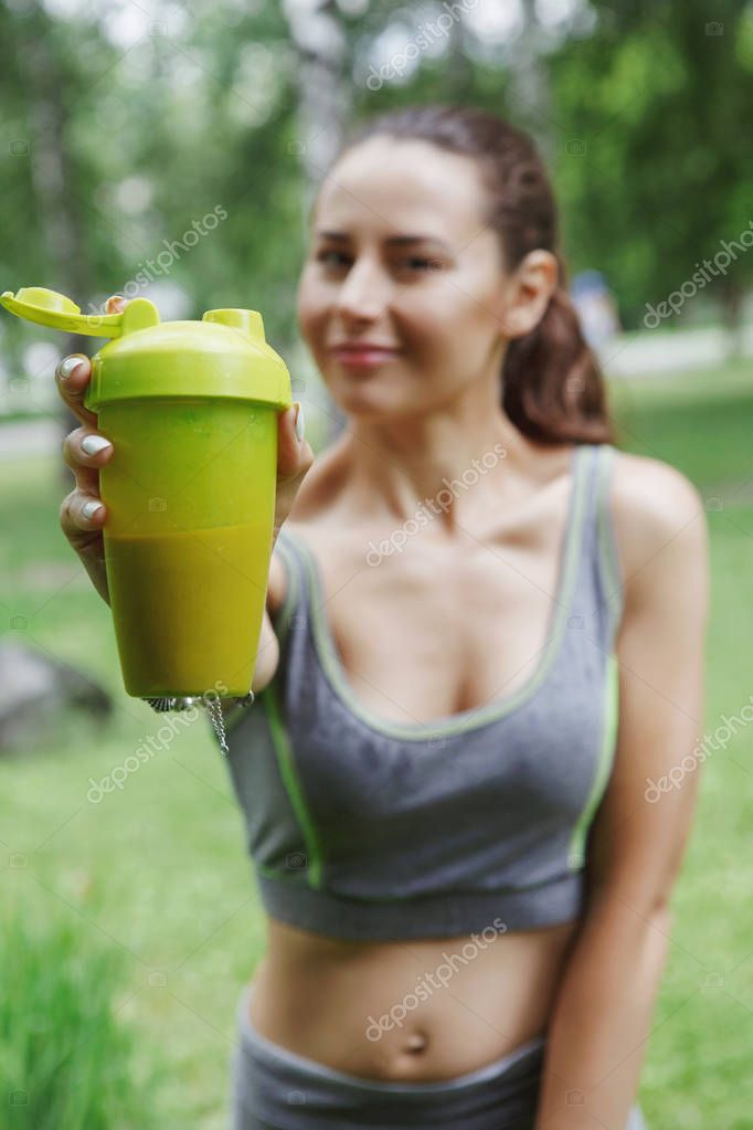 young pretty woman drinking energy drink while jogging