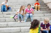 Különböző nemzetiségű iskolások csoportja, színes ruhában, akik kőlépcsőn ülnek. Tinédzserek beszélgetnek, zenét hallgatnak fejhallgatón, könyveket olvasnak.