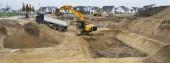 Fotografie Bagger und LKW arbeiten in Baugrube