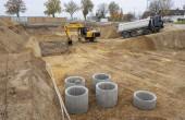Bagger und LKW arbeiten in Baugrube