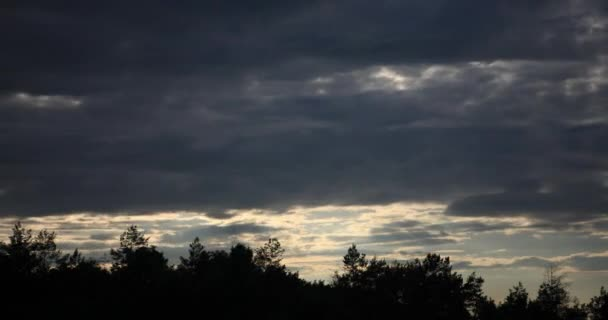 Quickly floating dark clouds in cloudy twilight and sunset
