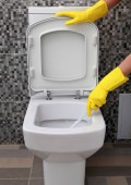 cleaning of white toilet bowl in yellow rubber gloves