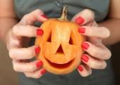 Malé žluté dýně v rukou během oslav Halloween