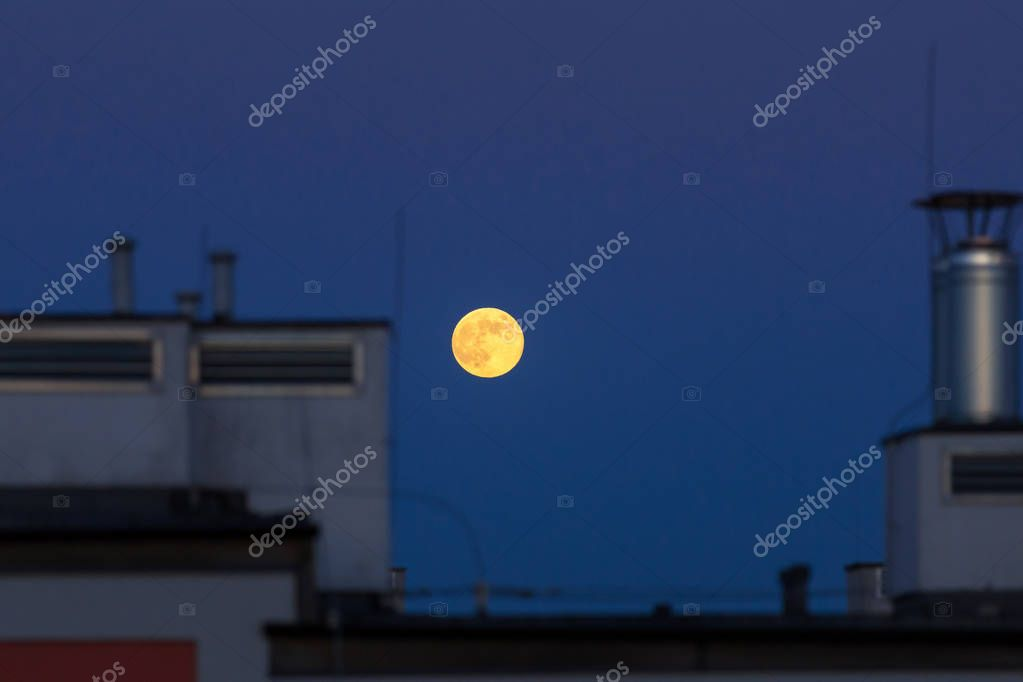 Full moon over the house roof