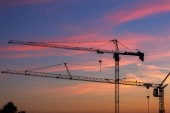 Photo Silhouette of tower cranes at construction site