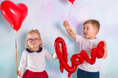 Little boy and girl toddlers with red heart balloons. Valentines day concept.