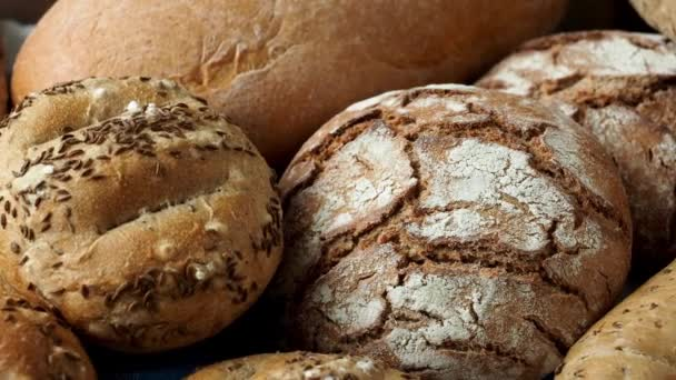Haldy chleba různých rolích posypané solí a kmínem, sezamem. Čerstvý Selský chléb z kynutého těsta