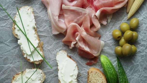 Hideg előétel. Felvágottak. Különböző ételek fehér gyűrött papír, sonka, kenyér, zöldség, felülről.