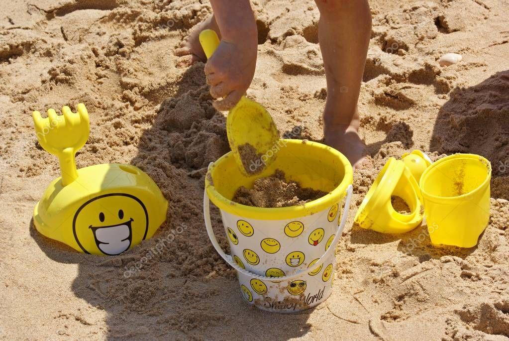 Kind spielt mit Sandeimer am Strand
