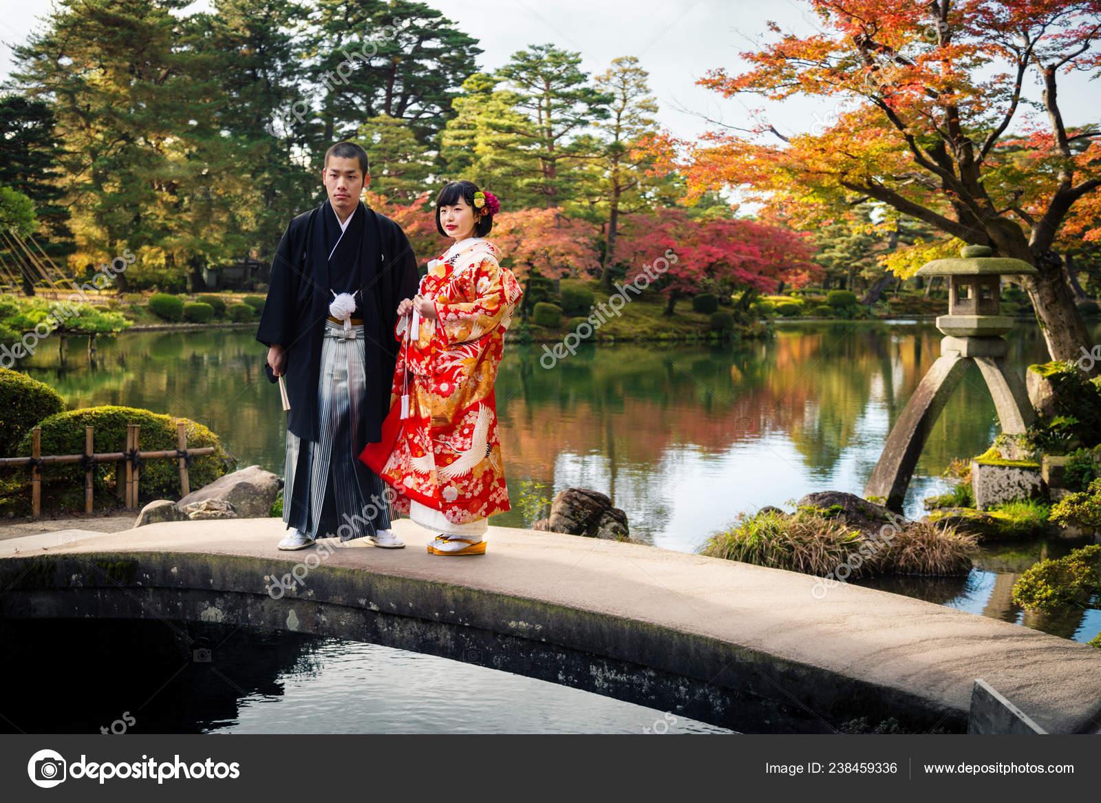 Japanese Wedding Kimono.Japanese Wedding Couple In Traditional Kimono Stand On A Bridge In