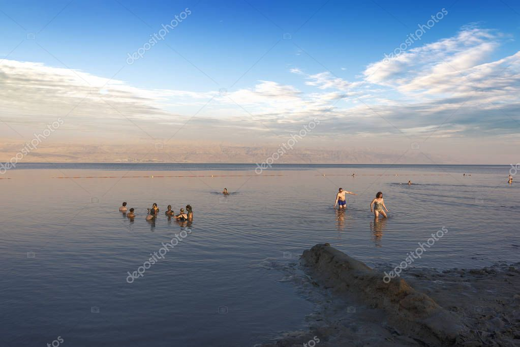 Dead Sea, Israel, May 05, 2017 : Photo of people  floating on surface Dead Sea enjoy summer sun and vacation. Recreation tourism, healthy lifestyle, free time concept