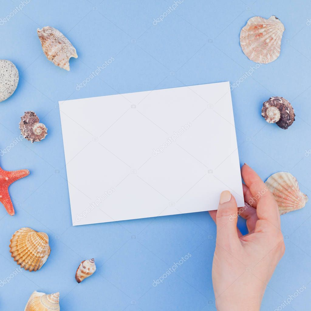 Creative square flat lay concept of summer travel vacations. Top view of seashells and starfish on pastel blue background with postcard mock up and copy space in minimal style, template for text