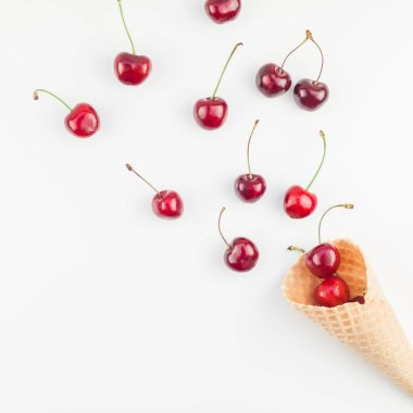 Square Creative top view of ripe cherries in a waffle cone with copy space isolated on white background in minimal style. Concept of summer fun and healthy eating. Template for your text or design.