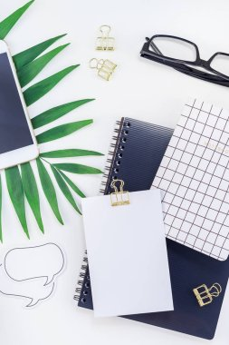 Top view flat lay office workspace desk styled design office supplies tropical palm leaves smartphone copy space black white background. Template office feminine blog social media