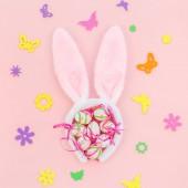 Kreativ Draufsicht flach legen Urlaub Zusammensetzung Ostereier Hasenohren Frühling Blumen auf rosa Papier Hintergrund Kopierraum Vorlage Ostern Tag saisonale Muster