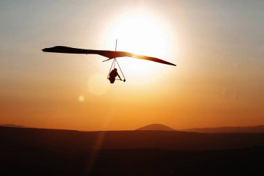 Hang-glider  flight in sky in sunset time over the
