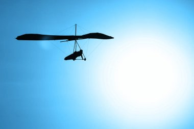 Hang-glider silhouette in sky in sunset time