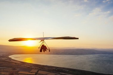 Hang-glider  flight in sky in sunset time over the Kineret, Mevo
