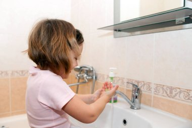 little girl washing her hands with soap by   sink