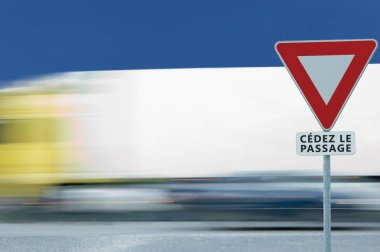 Give way yield french cedez le passage road sign, motion blurred truck vehicle traffic background, white signage triangle red frame regulatory warning, metallic pole post, blue summer sky, panneau signalisation cedez-le-passage, France