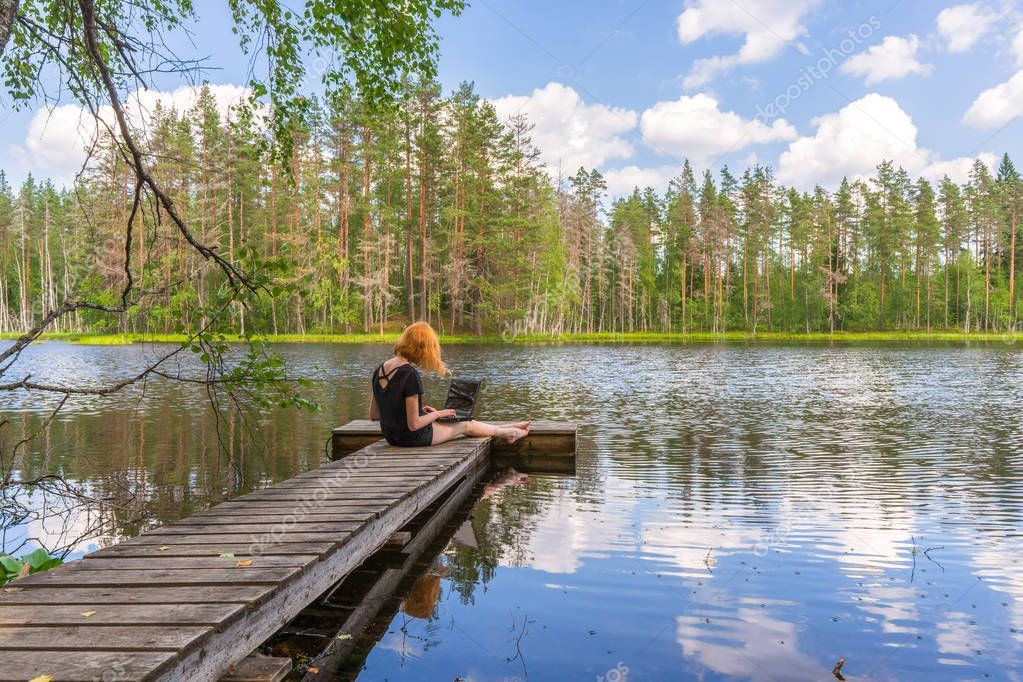 Cute ginger girl sitting on wooden planked footway and working with laptop in summer day against beautiful landscape of northern lake and forest. Freelance, work and travel concept. Karelia, Russia