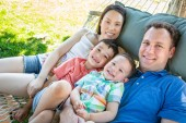 Caucasian Father and Chinese Mother Relaxing In Hammock with Mixed Race Sons