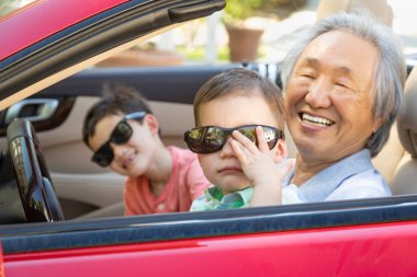 Chinese Granfather and Mixed Race Children Playing in Parked Car.