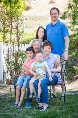 Chinese and Caucasian Family Sitting on Bench.