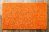 Fotografie Blank Orange Welcome Mat On Wood Floor Background Ready For Your Own Text.