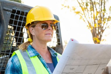 Female Worker Holding Technical Blueprints Near Small Bulldozer At Constrcution Site