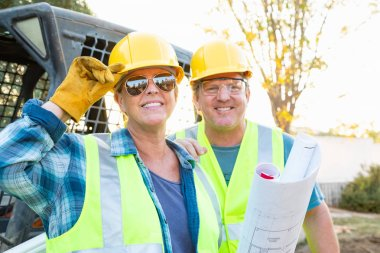 Male and Female Workers With Technical Blueprints at Construction Site