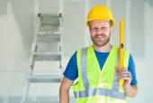 Fotografie Kavkazská mužské dodavatel s přilbou, úroveň a bezpečnostní vesta na staveništi