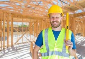 Caucasian Male Contractor With Hard Hat, Level and Safety Vest At Construction Site.