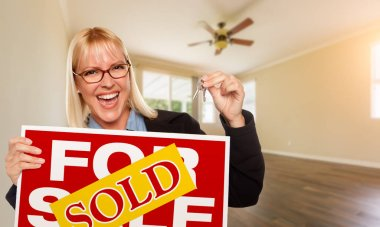 Attractive Young Woman with New Keys and Sold Real Estate Sign In Empty Room of House.