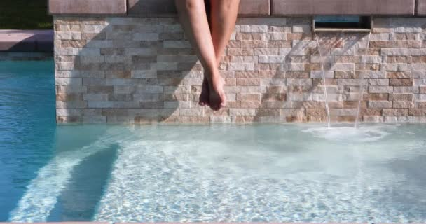 4k Looping Seamless Cinemagraph of Woman Swinging Feet Above Swimming Pool Water.