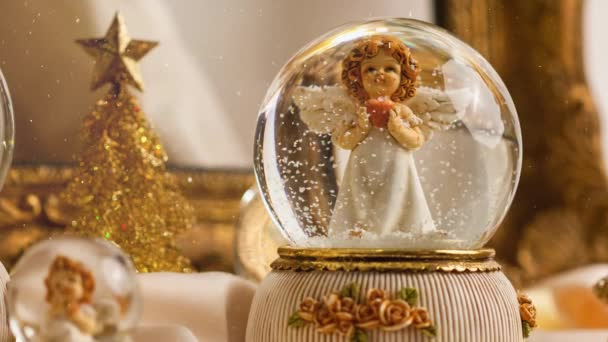 Footage of Christmas angel in snow globe decoration for the advent season with snowfall effect