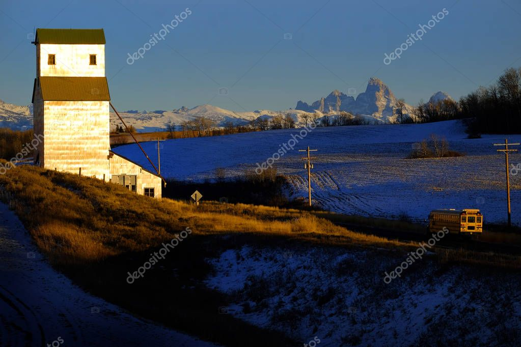 Old abandoned grainary grainery building with snow and Tetons Teton mountains school bus