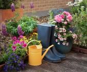 zahradnické nářadí a květiny na terase v zahradě