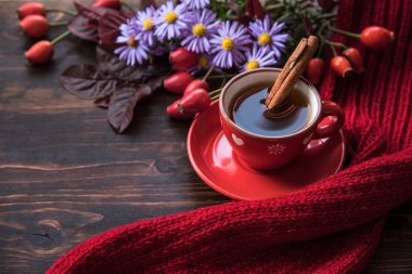 Autumn background with cup of tea, flowers  and warm scarf on the wooden background. Autumn still life, spending autumn time at cozy home