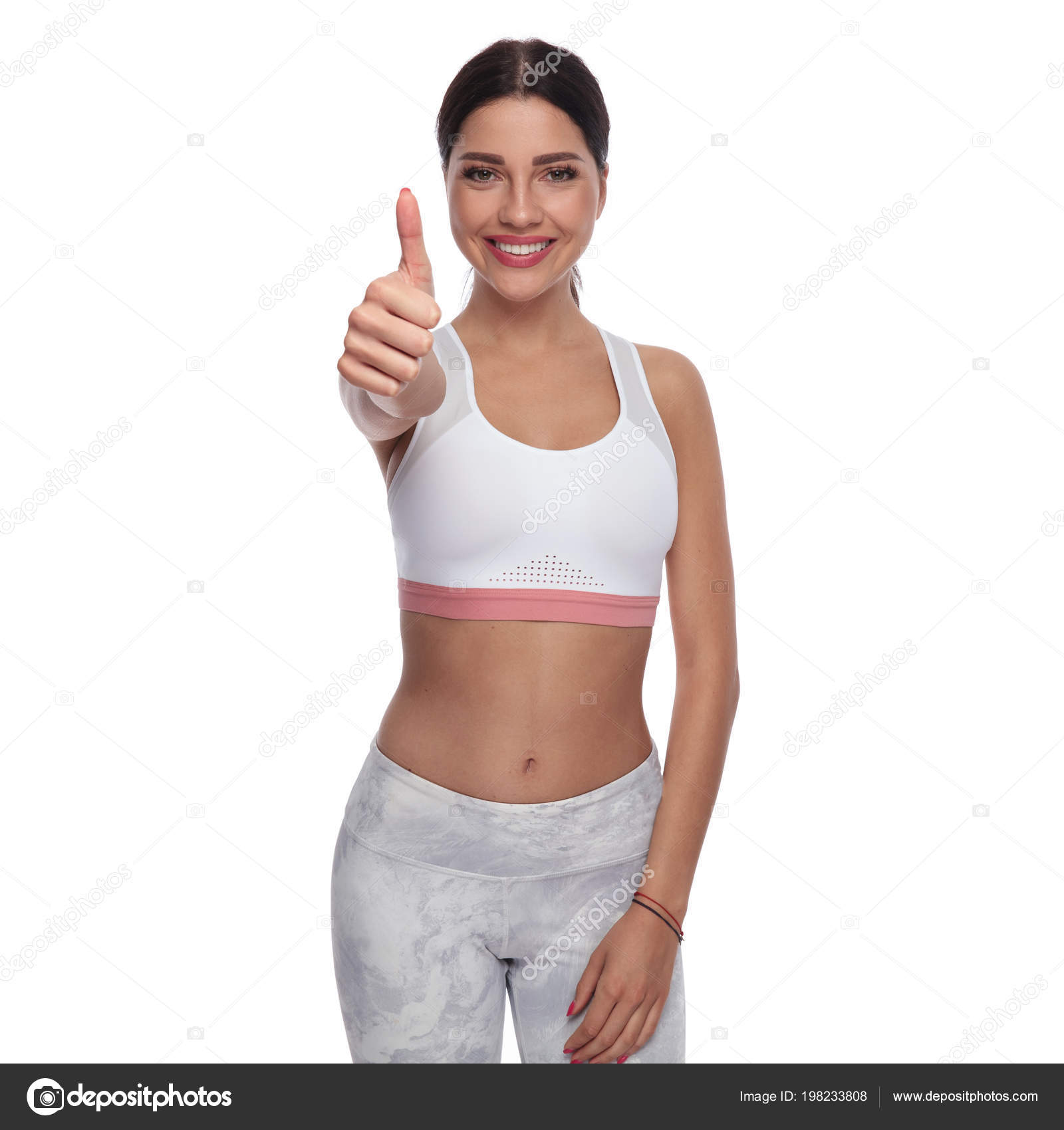Portrait Smiling Fit Woman Making Thumbs Sign While Standing