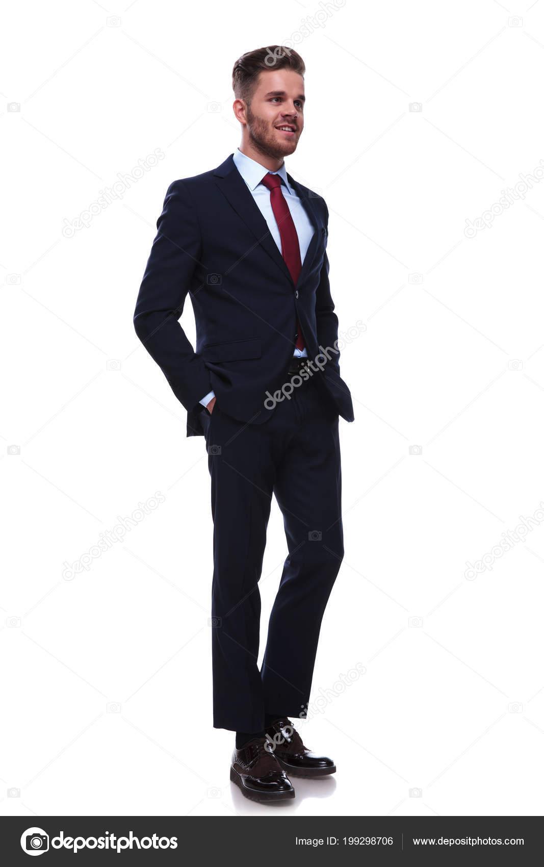 966764102fb4b Sexy homme d'affaires décontractée dans Marine costume et une cravate rouge  ressemble à côté lorsque vous êtes debout sur fond blanc — Image de feedough