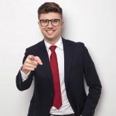 Fotografie usmívající se podnikatel s brýlemi a oblek body prstem přitom stát na světle šedém pozadí, portrétní obrázek