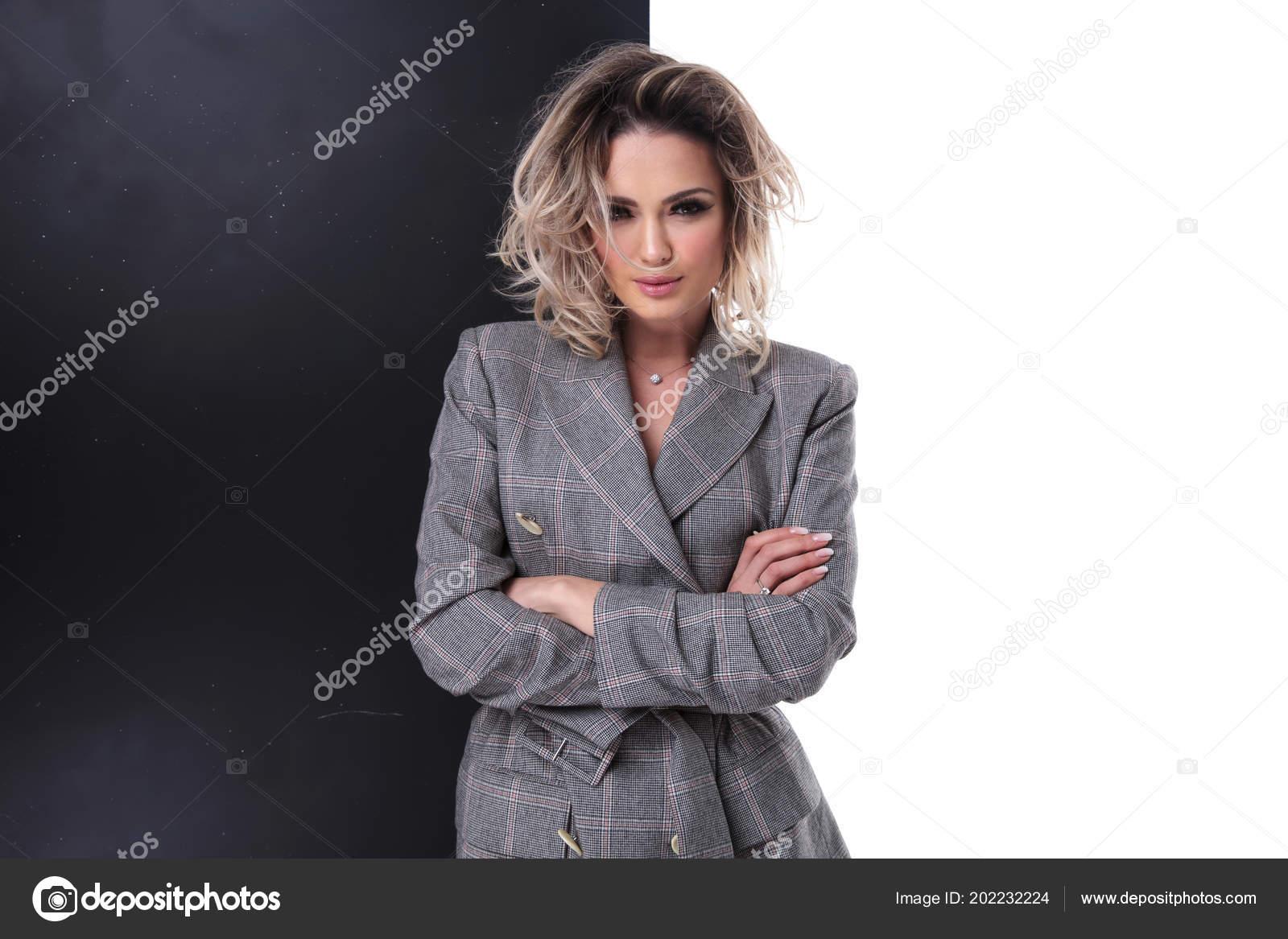 Πορτρέτο του νεαρή σέξι ξανθιά κοπέλα φορώντας γκρι καρό παλτό με τα χέρια  σταυρωμένα στέκεται σχετικά με μαύρο το μισό 9de1eb36443