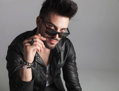 portrait of seductive man wearing leather jacket looking over sunglasses while sitting on light grey background and smiling